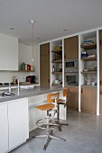 Island counter, retro swivel bar stools and minimalist pendant lamp with bulb in modern, open-plan kitchen