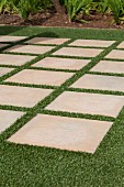 Terrace made from widely spaced stone flags laid in artificial lawn