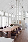 Dining area with upholstered chairs around wooden table in front of stove pipes and half-height partition wall in modern, white interior