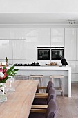 Detail of dining area in open-plan kitchen with gas hob on minimalist counter, fitted appliances and fitted cupboards with glossy white fronts