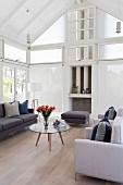 Sofa and armchairs in various shades of grey around retro coffee table in high-ceilinged interior