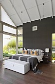 Double bed and white trunk in modern bedroom with wall painted dark grey
