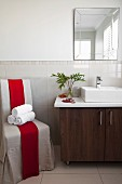 Rolled towels on loose-covered chair with red sash next to washstand with base cabinets and countertop basin