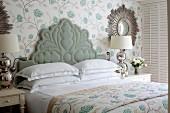 Bed with ornate upholstered headboard in elegant bedroom