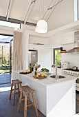 White open-plan kitchen with island counter and exposed beams in open roof area