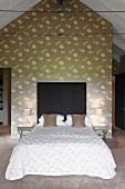 Double bed with dark headboard against wall with floral pattern