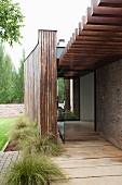 Veranda mit skulpturalen Holzelementen und Glastür