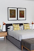 Symmetrical bedroom in shades of grey; scatter cushions with graphic pattern on box-spring bed below two artworks on wall