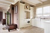 Offener Kochbereich mit hellen Schrankfronten im Landhausstil, seitlich Polsterhocker mit Lederbezug an braun getönter Wand in Wohnraum