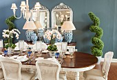 Elegant gedeckter Esstisch mit Peddigrohrstühlen und antiken Accessoires