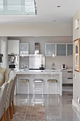 Modern kitchen in shades of grey, plexiglas bar stools at island counter and dining chairs in foreground