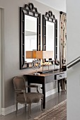 Dark console table next to Baroque armchair below two black-framed mirrors in elegant hallway