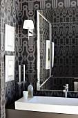 Mirror in elegant bathroom with expressive wallpaper and long designer sink