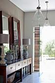 Holzrahmenspiegel, Amphoren und Tischlampen auf Sideboard im Kolonialstil und Pendelleuchten mit Glasschirmen