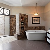 Free-standing bathtub in bathroom with stone tiles and pebble tiles