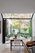 Blick vom Esstisch durch geöffnete Terrassentür in den Garten