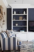 White, fitted shelving against dark blue wallpaper in living room