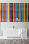 Mosaic of colourful wide stripes above white designer bathtub