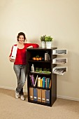 Woman standing next to black shelving unit with floating white magazine trays on one side