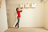 Woman holding box next to storage boxes hung on wall