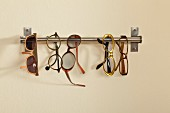 Spectacles hung on stainless steel rod mounted on wall