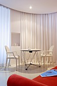 White Ghost Chairs at table in front of white curtain partition; orange sofa in foreground