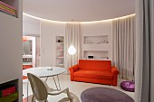 Orange sofa, white table and designer pendant lamps in circular modern apartment with white curtains as partitions