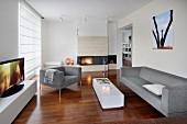 Elegante Sofagarnitur in Hellgrau und weisser Bodentisch in modernem, offenem Wohnraum, Kaminfeuer im Hintergrund, seitlich geschlossenes Rollo an Fenstertür