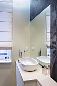 Washbasin on base unit in front of mirror integrated in wall in corner of modern bathroom