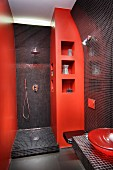 Small bathroom with indirect lighting behind black mosaic-tiled panels, orange wall elements and matching basin
