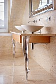 Twin sinks on wooden counter with stone slab surface and supports in shape of dancers legs en pointe in bathroom with stone wall and floor tiles