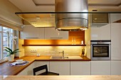 Stainless steel extractor hood with glass panel in modern kitchen with white cupboards and indirect lighting above kitchen counter