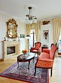 Sitzbank mit rotgoldenem Ornament Muster auf Stoffbezug in Barock Stil, antiker Couchtisch, vor Kamin in herrschaftlicher Wohnzimmerecke