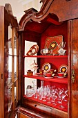 Antique, Art Nouveau crockery and glasses on red shelves in open. Baroque-style display cabinet