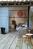 Wooden stools and wicker trunk on wooden terrace in front of sliding door leading to bedroom