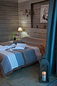 Double bed with striped bedspread in shades of brown and blue and table lamp in corner of wood-clad room with floor lantern in foreground