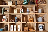 Vintage cooking utensils such as poppy seed grinders and poppy seed heads on simple wooden shelves
