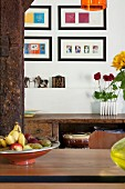 View past fruit bowl on dining table to gallery of modern pictures above rustic battered sideboard