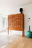 Vintage wooden apothecary cabinet and turquoise floor vase on wooden floor in minimalist interior