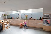 Long kitchen counter with pale wooden doors and pale blue splashback in kitchen-dining room; little girl playing