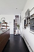 Metal staircase in designer kitchen with black, tiled floor