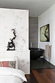 Subtle floral wallpaper on partition with ethnic sculpture on shelf and view of free-standing bathtub in ensuite bathroom
