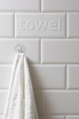 Towel hanging from suction cup hook on tiled wall