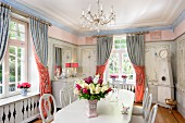 White table and chairs with carved backrests in dining room with decoratively painted walls and draped curtains on windows
