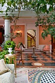 Wintergarten mit Grünpflanzen vor Salon mit Fliesenboden im Schachbrettmuster und Säulenreihe