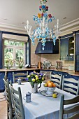 Dining table, pale grey chairs and chandelier made from coloured glass in kitchen with cupboards painted blue