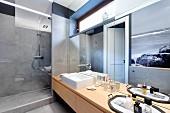 Spiegelfront hinter Waschtisch mit Aufsatzbecken, daneben begehbare Dusche