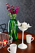 Still-life arrangement of green glass vase, retro wire basket, white china mugs with knitted surface texture and candlestick