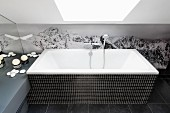Bathtub with black mosaic-tiled surround against photo mural of mountains below skylight