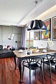 Eklektizistischer Stil in offenem Wohnraum, moderne Lounge mit Stehleuchte vor Sichtbetonwand